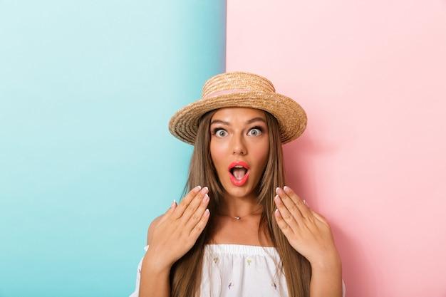 Zszokowana młoda piękna kobieta pozuje na białym tle na sobie kapelusz.
