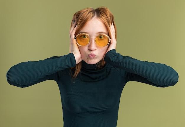 Zszokowana młoda ruda dziewczyna imbir z piegami w okularach przeciwsłonecznych, trzymając głowę i patrząc na kamery na oliwkowej zieleni