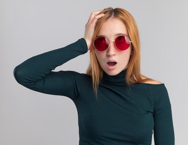 Zszokowana młoda ruda ruda dziewczyna z piegami w okularach przeciwsłonecznych kładzie rękę na głowie i patrzy w górę na białym tle na białej ścianie z miejscem na kopię