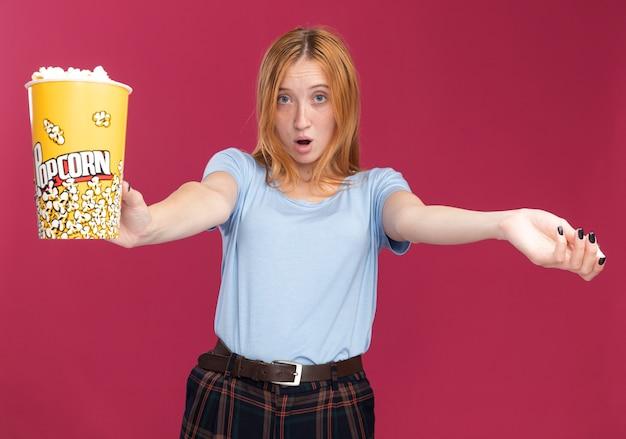 Zszokowana młoda rudowłosa ruda dziewczyna z piegami trzyma wiadro popcornu izolowane na różowej ścianie z miejscem na kopię