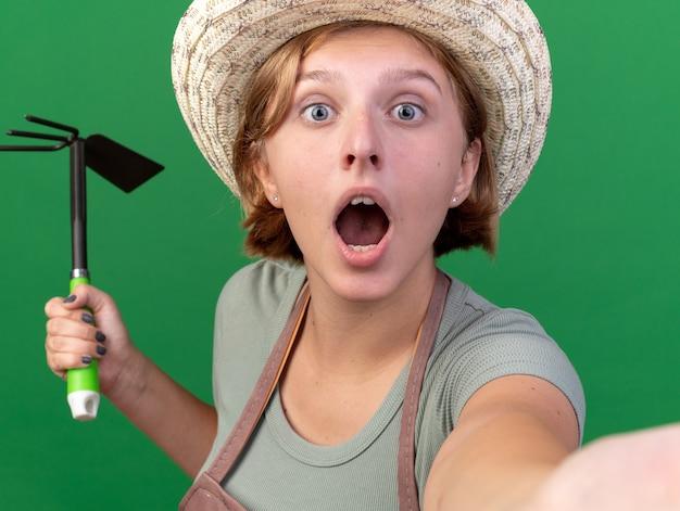 Zszokowana młoda słowiańska ogrodniczka w kapeluszu ogrodniczym, trzymająca grabie motyka i robiąca selfie na zielonej ścianie z miejscem na kopię