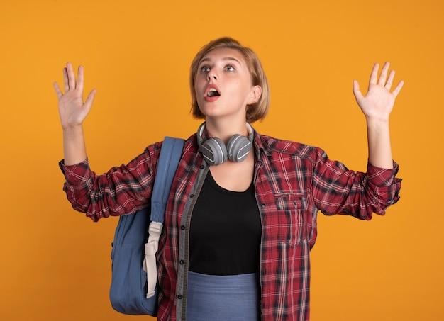 Zszokowana młoda słowiańska studentka ze słuchawkami, nosząca stojaki na plecaki z uniesionymi rękami