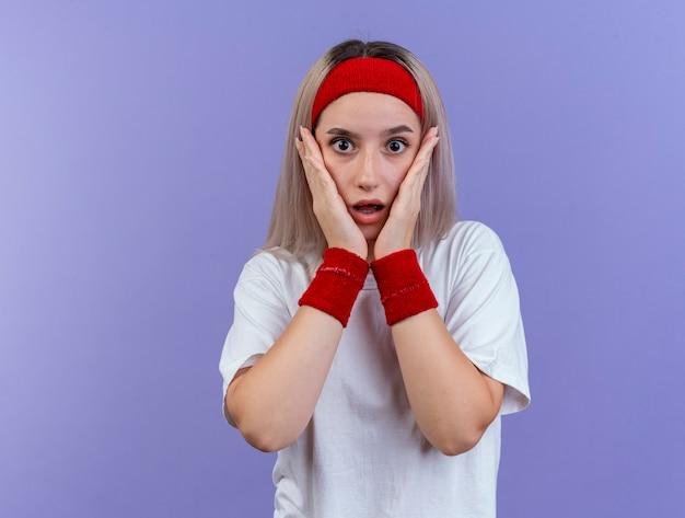 Zszokowana młoda sportowa kobieta z szelkami, nosząca opaskę i opaski na nadgarstkach, kładzie ręce na twarzy odizolowanej na fioletowej ścianie