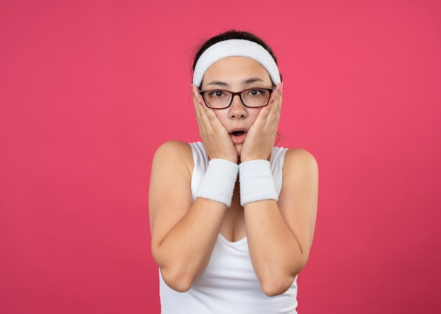 Zszokowana młoda wysportowana dziewczyna w okularach optycznych, nosząca opaskę na głowę i opaski, kładzie ręce na twarzy