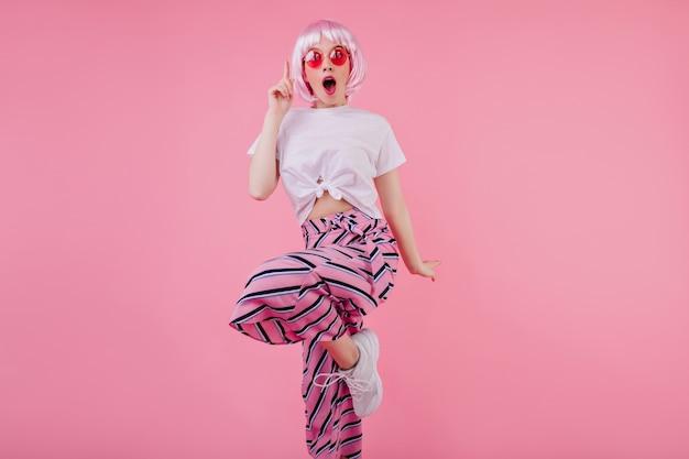 Zszokowana modelka w eleganckiej różowej peruke tańczy w modnych ciuchach. wewnątrz wytworna dziewczyna w peruce wyrażająca zdumione emocje