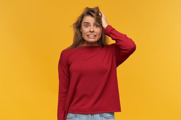 Zszokowana niezadowolona blondynka wygląda z oburzeniem, usta szeroko otwarte, zamarła z oburzenia, ubrana w swobodny czerwony sweter