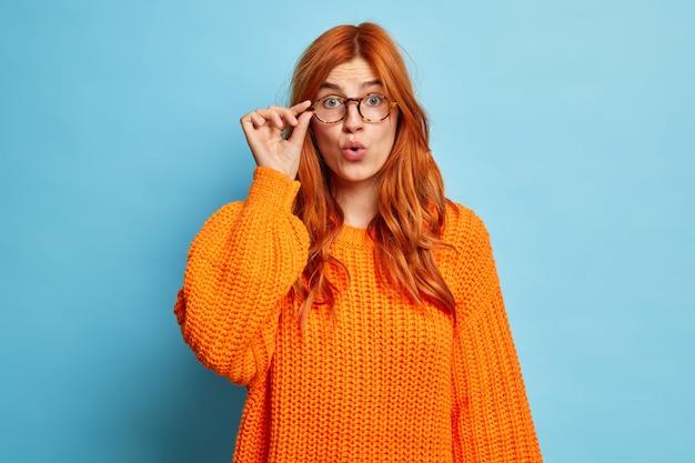 Zszokowana, oniemiała europejka o rudych włosach, trzymająca dłoń na okularach, patrzy z wielkim zdziwieniem ubrana w dzianinowy pomarańczowy sweter, otwierając usta z nieoczekiwanych emocji.