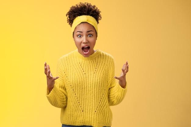 Zszokowana oszołomiona afroamerykanka rozczarowana kobieta nie może uwierzyć przyjaciółka pomieszana projekt wygląda na sfrustrowaną zirytowaną zdenerwowaną narzekającą kłócącą się podnoszącą ręce przerażeniem zakwestionowanym spojrzeniem kamery.