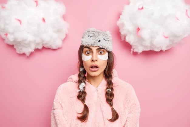 Zszokowana, oszołomiona młoda dziewczyna niespodziewanie wpatruje się w aparat, trzymając usta otwarte przed zdumieniem, nosi hydrożelowe plastry pod oczami, zdaje sobie sprawę, że spóźnia się do pracy