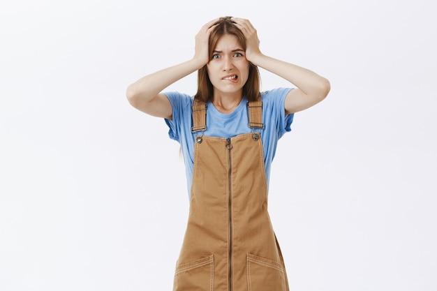 Zszokowana panikująca kobieta łapie się za głowę i wygląda na zaniepokojoną, ma duży problem