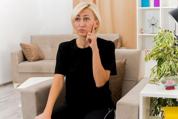 Zszokowana piękna blondynka rosjanka siedzi na fotelu kładąc palec na twarzy patrząc z boku wewnątrz salonu