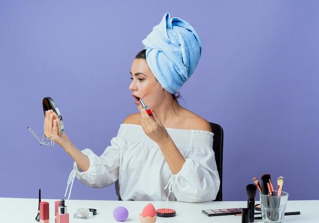Zszokowana piękna dziewczyna owinięty ręcznikiem do włosów siedzi przy stole z narzędziami do makijażu, trzymając szminkę patrząc w lustro na fioletowej ścianie