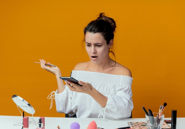 Zszokowana piękna dziewczyna siedzi przy stole z narzędziami do makijażu, patrząc na telefon trzymając pędzel do makijażu na białym tle na pomarańczowej ścianie