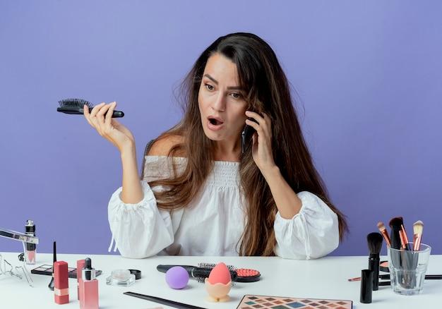 Zszokowana piękna dziewczyna siedzi przy stole z narzędziami do makijażu trzyma grzebień do włosów, rozmawia przez telefon, patrząc na bok na białym tle na fioletowej ścianie
