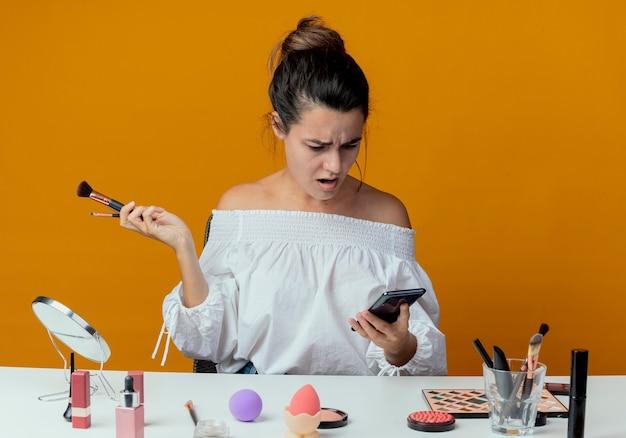 Zszokowana piękna dziewczyna siedzi przy stole z narzędziami do makijażu trzyma pędzle do makijażu, patrząc na telefon na białym tle na pomarańczowej ścianie