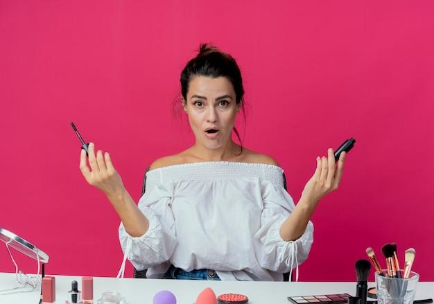 Zszokowana piękna dziewczyna siedzi przy stole z narzędziami do makijażu trzyma tusz do rzęs na białym tle na różowej ścianie