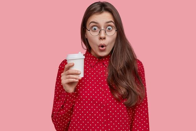 Zszokowana piękna kobieta trzyma kawę na wynos, otwiera usta, zaskoczona plotkami