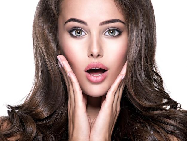 Zszokowana piękna kobieta z otwartymi ustami szuka. na białym tle portret zbliżenie na białym tle