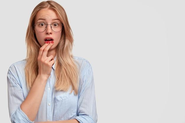 Zszokowana piękna młoda kobieta o oszołomionym wyrazie twarzy, ma otwarte usta, zastanawia się nad najnowszymi wiadomościami, ubrana w elegancką koszulkę