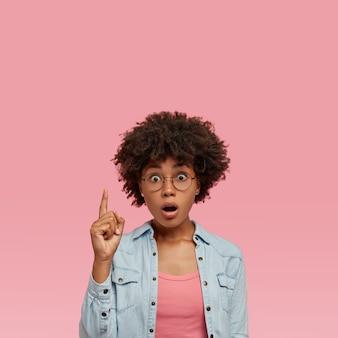 Zszokowana piękna nastolatka hipster o ciemnej skórze, z otwartymi ustami, ubrana w modną dżinsową koszulę, wskazuje palcem wskazującym w górę, będąc pod wrażeniem zauważenia dziury w suficie, modelki w pomieszczeniach