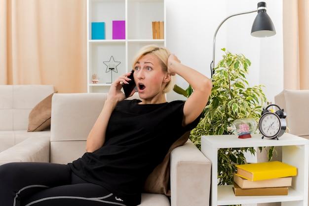 Zszokowana piękna rosjanka blondynka, leżąc na fotelu, kładąc rękę na głowie za rozmową przez telefon wewnątrz salonu