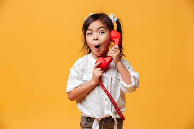 Zszokowana podekscytowana dziewczynka rozmawia przez czerwony telefon retro.