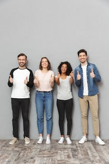 Zszokowana, podekscytowana grupa przyjaciół podnosi kciuki.
