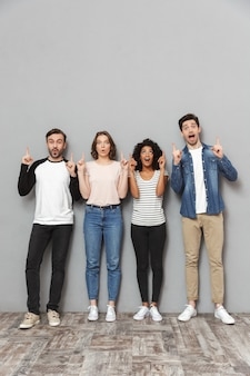 Zszokowana podekscytowana grupa przyjaciół stojących na białym tle