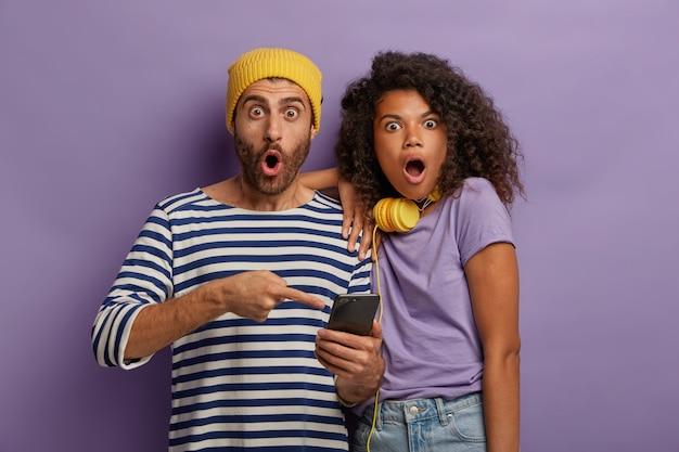 Zszokowana, przerażona kobieta i mężczyzna rasy mieszanej czytają wiadomości e-mail na smartfonie, otrzymują przerażające wiadomości,