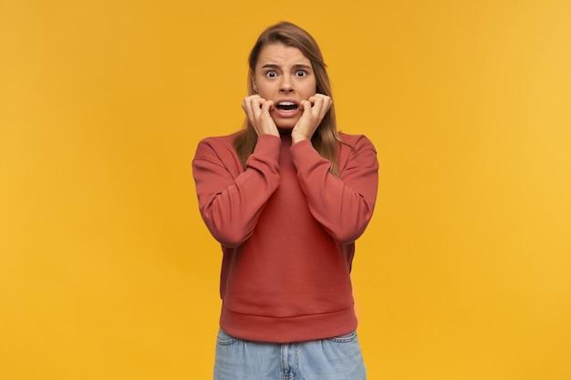 Zszokowana, przerażona młoda kobieta w zwykłym ubraniu krzyczy i boi się żółtej ściany.