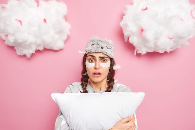 Zszokowana przestraszona dziewczyna z dwoma warkoczykami martwiąca się widokiem koszmaru nosi na czole maskę do spania