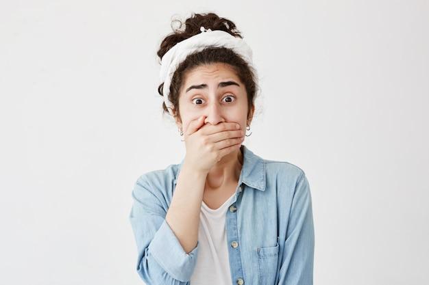 Zszokowana przestraszona młoda brunetka w szmatce i dżinsowej koszuli zakrywającej usta dłonią trzymającą w tajemnicy. ciemnowłosa młoda kobieta nie chce szerzyć plotek, pozuje z wytrzeszczonymi oczami