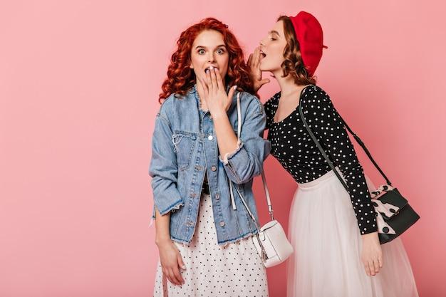 Zszokowana ruda dziewczyna słuchająca przyjaciela. dwie kobiety rozmawiają na różowym tle.
