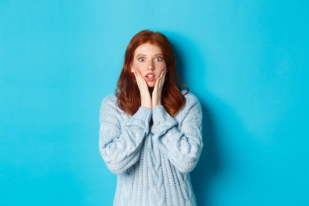 Zszokowana ruda dziewczyna wpatrująca się w kamerę oniemiała, wyrażająca niedowierzanie i zdumienie, stojąca w swetrze na niebieskim tle.
