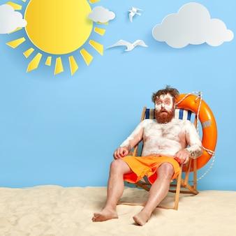 Zszokowana ruda pozuje na plaży z filtrem przeciwsłonecznym