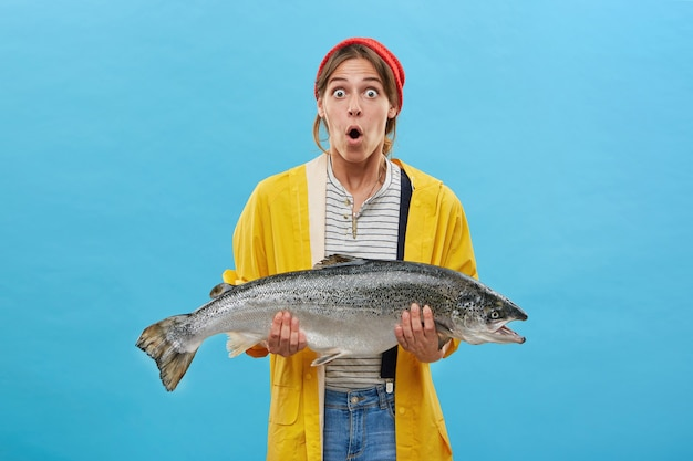 Zszokowana samica trzymająca ogromną rybę, która