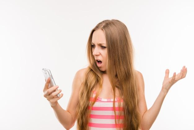 Zszokowana sfrustrowana młoda kobieta z telefonem