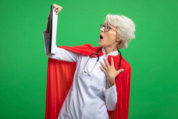 Zszokowana słowiańska superbohaterka w mundurze lekarza z czerwoną peleryną i stetoskopem w okularach optycznych