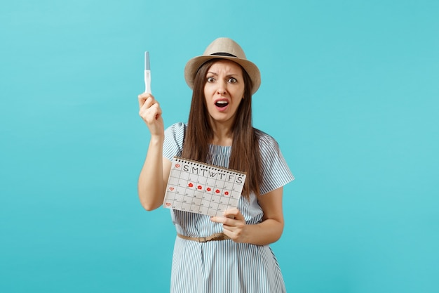 Zszokowana smutna kobieta w niebieskiej sukience, kapelusz trzymaj w ręku test ciążowy, kalendarz okresów do sprawdzania dni menstruacji na białym tle na niebieskim tle. medycyna, opieka zdrowotna, koncepcja ginekologiczna. skopiuj miejsce.