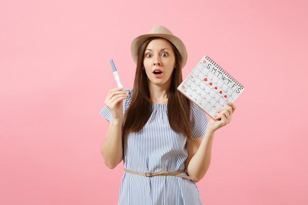 Zszokowana smutna kobieta w niebieskiej sukience, kapelusz trzymaj w ręku test ciążowy, kalendarz okresów do sprawdzania dni menstruacji na białym tle na różowym tle. medycyna, opieka zdrowotna, koncepcja ginekologiczna. skopiuj miejsce.