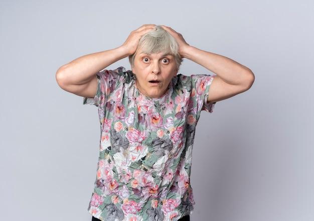 Zszokowana starsza kobieta kładzie ręce na głowie patrząc na białym tle na białej ścianie