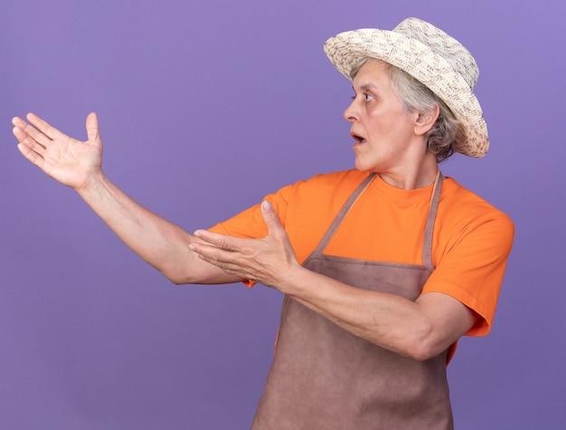 Zszokowana starsza kobieta ogrodniczka w kapeluszu ogrodniczym, patrząca i wskazująca na bok