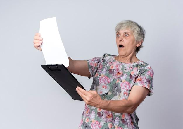 Zszokowana starsza kobieta trzyma i patrzy na schowek na białym tle na białej ścianie
