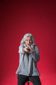 Zszokowana starsza kobieta zmienia kanał z pilot do tv przeciw czerwonemu tłu