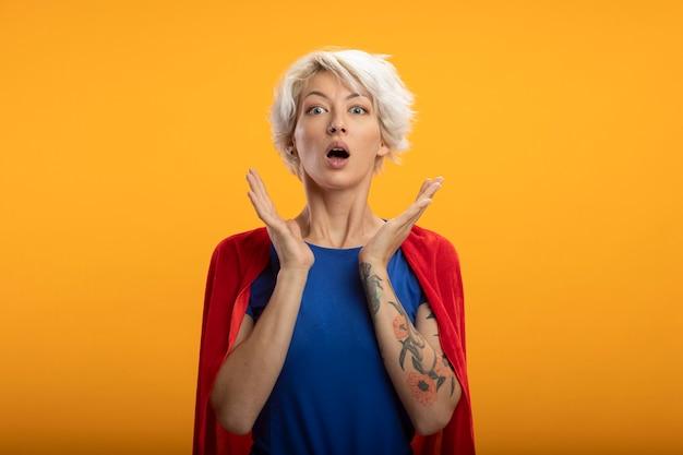 Zszokowana superwoman z czerwoną peleryną stojącą z uniesionymi rękami na białym tle na pomarańczowej ścianie