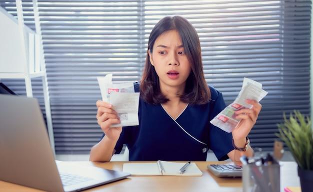 Zszokowana twarz azjatycka kobieta ręka trzyma rachunek wydatków i obliczenia na temat rachunków zadłużenia co miesiąc przy stole w domowym biurze.