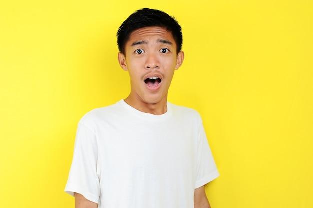 Zszokowana twarz azjatyckiego człowieka w białej koszuli na żółtym tle.