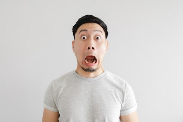 Zszokowana twarz azjatyckiego mężczyzny w szarej koszulce i szarym tle.