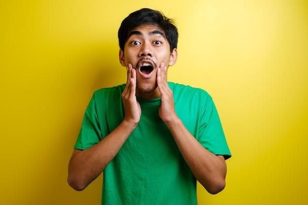Zszokowana twarz azjatyckiego mężczyzny w zielonej koszulce na żółtym tle