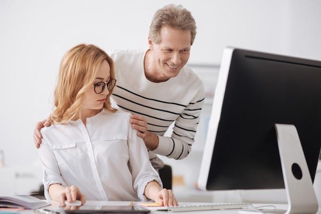 Zszokowana, urażona młoda sekretarka siedzi w biurze i pracuje nad projektem, wyrażając jednocześnie oburzenie wobec flirtu szefa